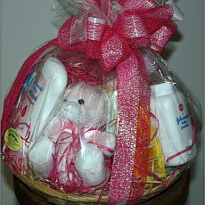 Pink baby hamper in basket with pink ribbon